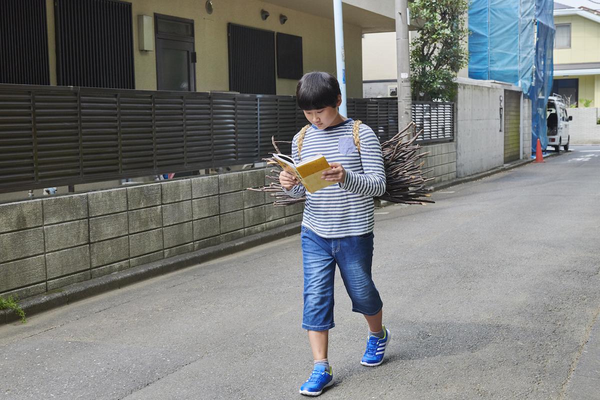薪を背負いながら本を読み歩く息子