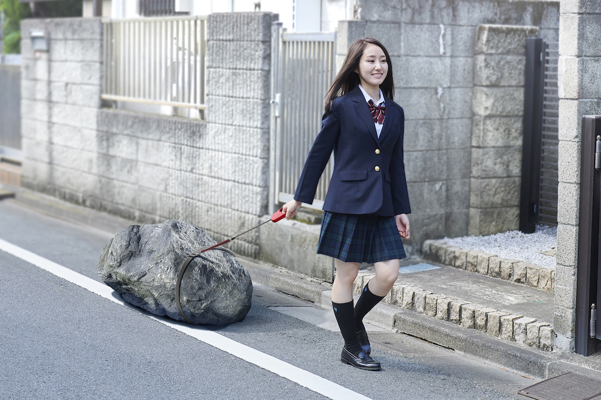 割と大きめの石を紐でつないで散歩させている娘