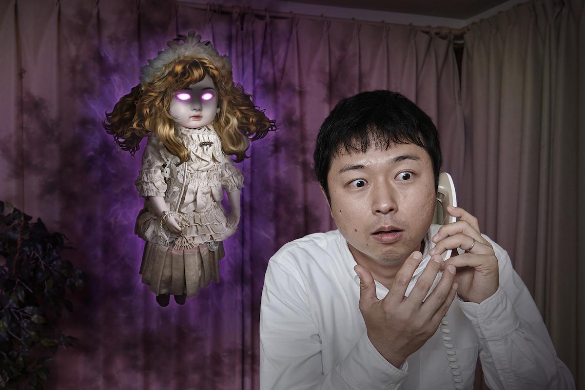 電話中の父と、背後に立っているフランス人形のメリーさん