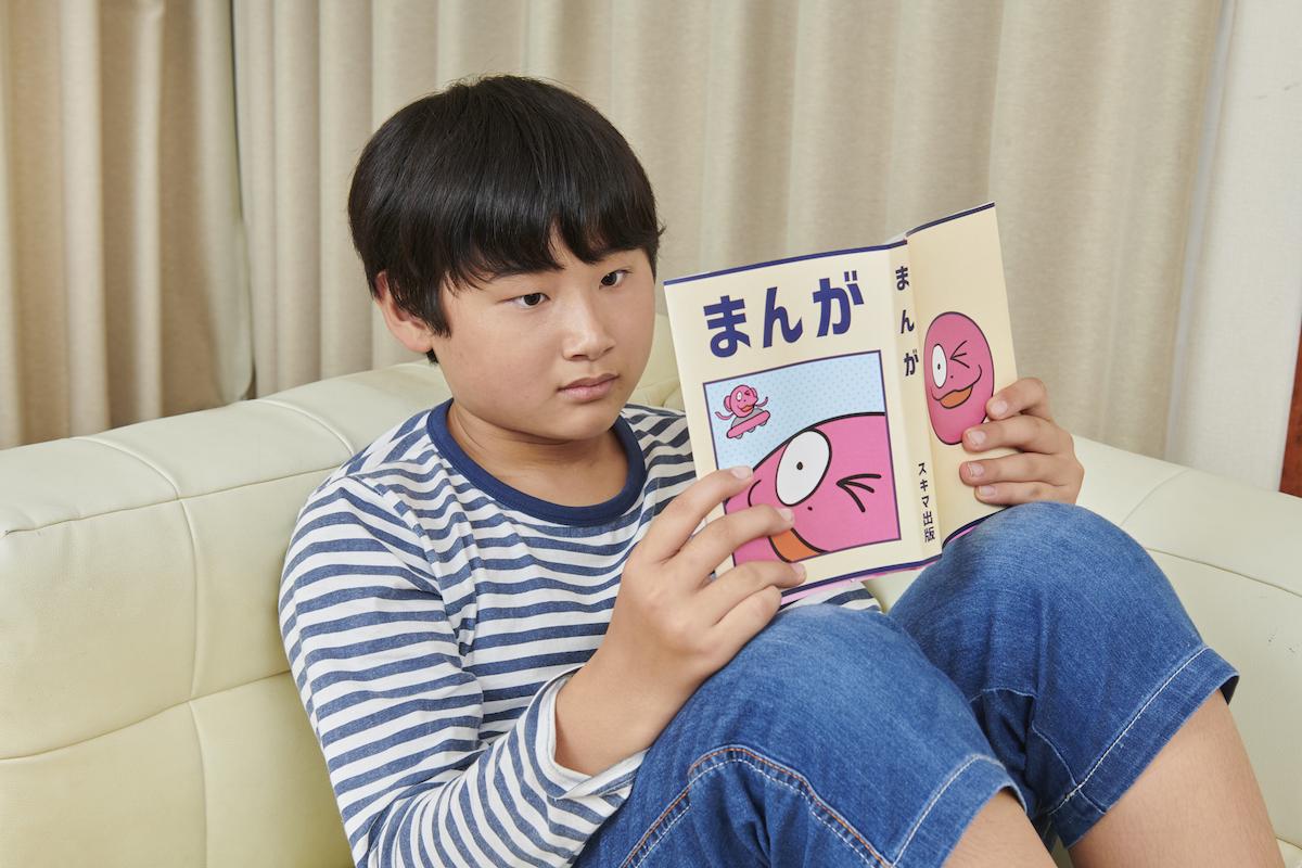 「まんが」と書いてあるまんが本を読んでいる息子