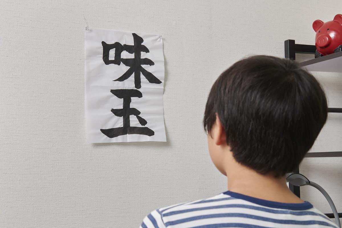 「味玉」と書かれた習字を部屋に貼る息子